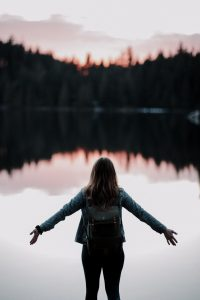 woman standing while facing on body of water